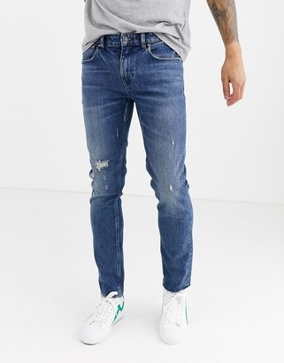 ASOS DESIGN Cone Mill Denim skinny 'American classic' jeans in mid wash blue with abrasions and raw hem