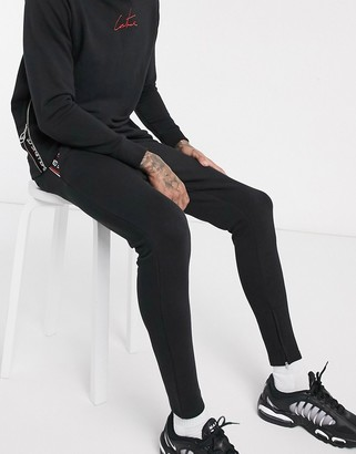 The Couture Club taped zip detail sweatpants in black