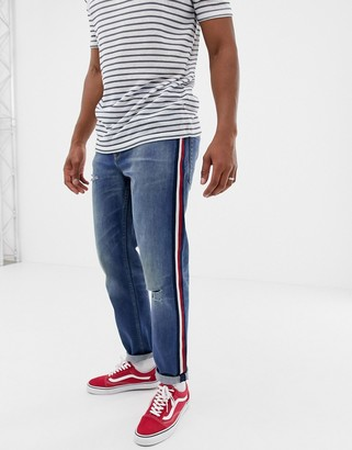 Asos DESIGN tapered jeans in mid wash blue with red side stripe
