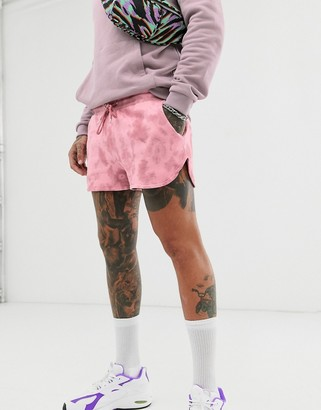 Asos Design DESIGN jersey runner shorts with tie dye wash-Pink