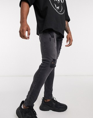 ASOS DESIGN spray on jeans in washed black with heavy rips