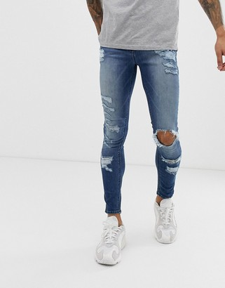ASOS DESIGN spray on jeans in power stretch with heavy rips in mid wash blue