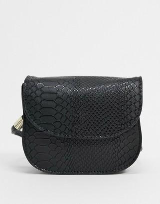 ASOS DESIGN cross body saddle bag in black snake