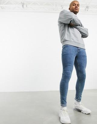 ASOS DESIGN spray on jeans in power stretch denim in light wash blue