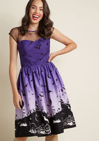 4770 Some may call this festive A-line dress spooky, but in your mind, the idea of going without it is even scarier! A purple, pin-up-inspired piece by Hell Bunny, this cotton frock flaunts a mesh illusion neckline with cute cap sleeves, a back keyhole, and a