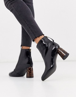 Glamorous black patent boots with leopard heel