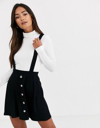 ASOS DESIGN button front mini pinafore skirt in black