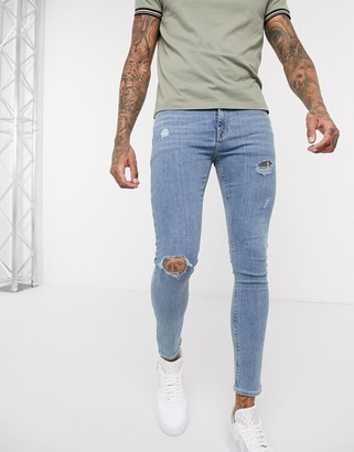 ASOS DESIGN spray on jeans in power stretch denim in light wash blue with abrasions