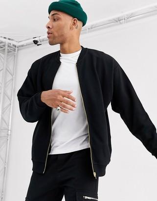 Asos Design DESIGN oversized jersey bomber jacket in black with gold side zips