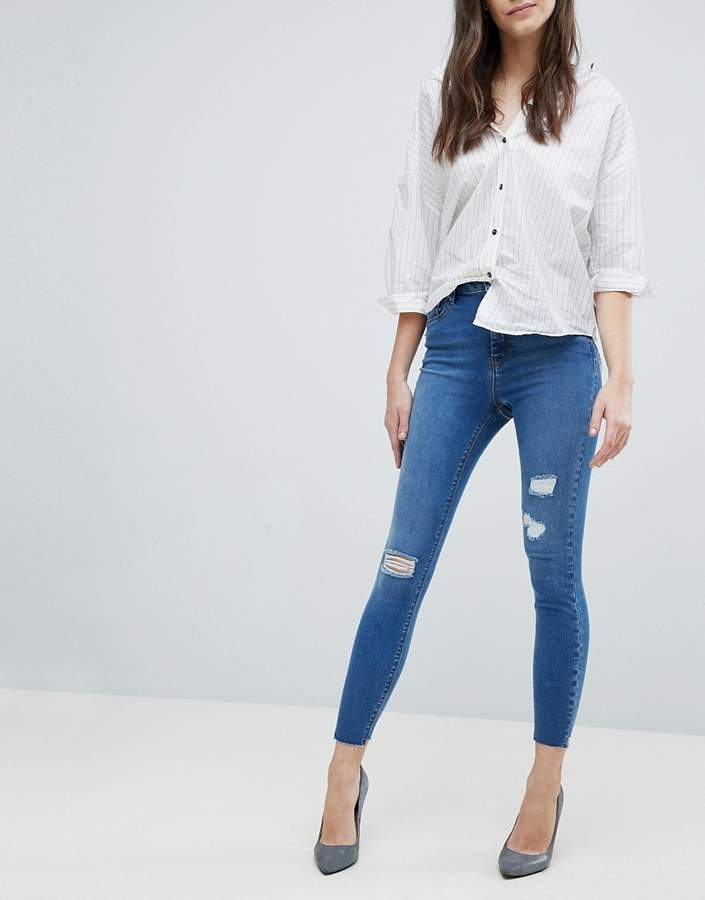 Asos Design DESIGN Ridley high waist skinny jeans in pretty mid wash with rip and repair and reverse Stepped hem