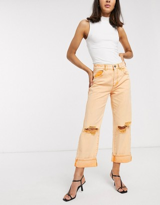 ASOS DESIGN low slung carpenter jeans with extreme rips in orange