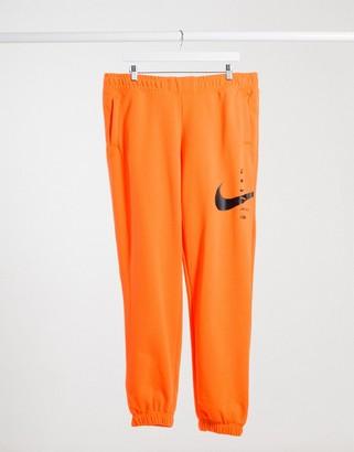 Nike swoosh fleece pant in orange and black