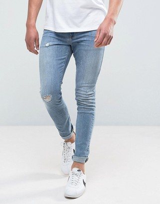 ASOS DESIGN super skinny jeans in mid wash blue with abrasions