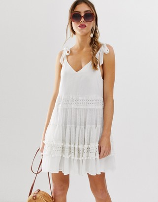 Asos Design DESIGN trapeze mini sundress with lace inserts and dobby pom pom trims-White