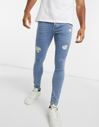 ASOS DESIGN spray on jeans with power stretch in light wash blue with abrasions