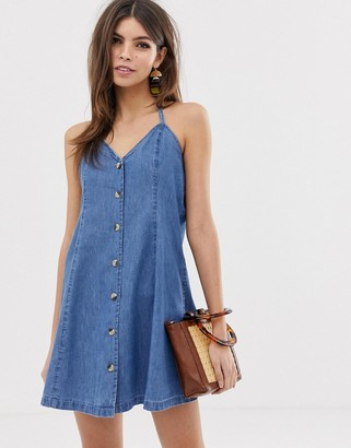 Asos DESIGN denim halter neck mini dress with buttons in midwash blue
