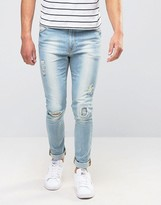 Asos Super Skinny Jeans With Patch Abrasions In Bleach Blue