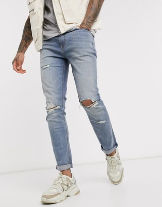 ASOS DESIGN skinny jeans in vintage mid wash blue with knee rips