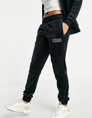 Puma velour joggers in black and gold