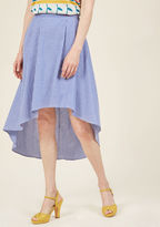 S94838 The magic of this chambray skirt can transform the even most casual gait into a show-stopping strut! While the pleats, high waistline, and white pinstripes of this blue beauty are all appreciated design elements, it's the wind-catching high-low hemline th