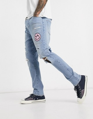 ASOS DESIGN drop crotch jeans in light wash blue with heavy rips and abrasions with patch