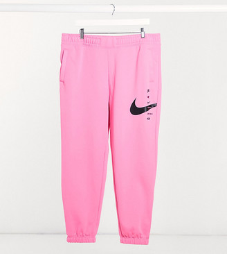 Nike Plus swoosh oversized joggers in pink