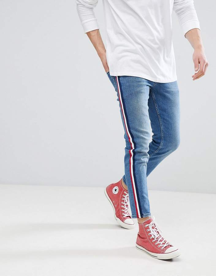 Asos DESIGN slim jeans in mid wash blue with white side stripe
