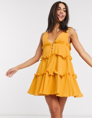 ASOS DESIGN button front tiered mini sundress in textured crinkle in mustard