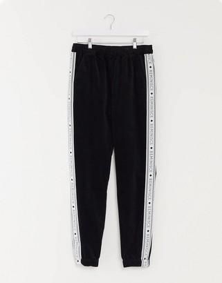 ASOS DESIGN slim joggers in black velvet with side stripe