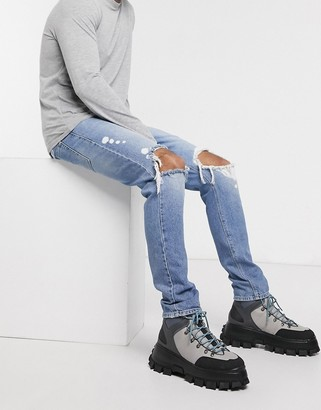 ASOS DESIGN drop crotch jeans in mid wash blue with heavy rips and bleach details