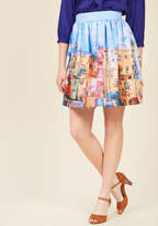 citymood No matter where you go in this beautiful blue skirt, you'll always feel right at home! The classic A-line silhouette of this stunning number is residence to a breathtaking painterly print of a quaint neighborhood accentuated by bold colors and a welcoming