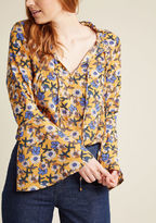 8164t The throwback bliss you'll experience from flaunting this mustard yellow blouse isn't limited to its debut wear! With its ruffled neckline situated snugly atop a pair of ties, beautiful bell sleeves, and fun floral print in ivory and cornflower hues, this