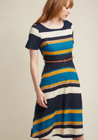 D0066-D Dignified and demure, this short-sleeved dress by Sugarhill Boutique colors your workday with above-ordinary appeal. Mingling navy, ivory, tan, marigold, and lake blue stripes, topped with a brown faux-leather belt, and falling to a comfortable knee lengt