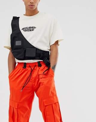 Asos Design DESIGN chest harness vest bag in black with pockets