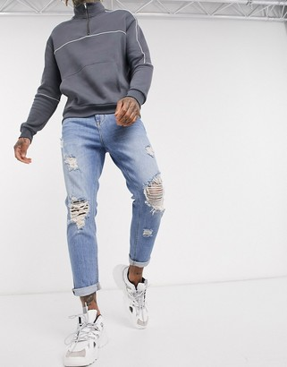 ASOS DESIGN tapered jeans in vintage light wash with heavy rips