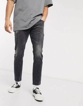 ASOS DESIGN slim jeans in washed black with raw hem and seam detail