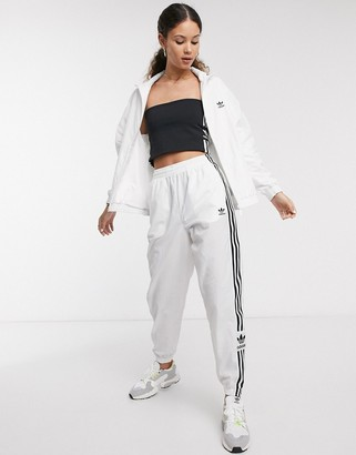 adidas adicolor locked up logo track pants in white
