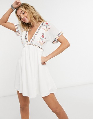 En Creme mini dress with ladder inserts and embroidered kimono sleeves