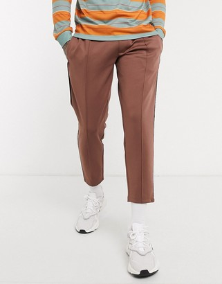 ASOS DESIGN tapered joggers in scuba fabric with pin tucks & piping in brown