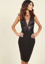 DR588 Call on the confidence-boosting attributes of this sultry frock to ensure sheer success at your cabaret debut! The shimmering sequined vines, plunging, mesh-accented neckline, and figure-hugging skirt of this bold LBD amplify your attitude, empowering you