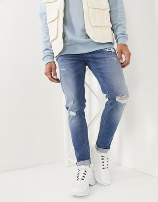 ASOS DESIGN skinny jeans in mid wash blue with rips and destroy