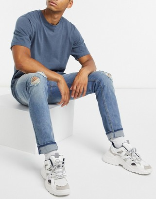 ASOS DESIGN skinny jeans in mid wash blue with knee rips