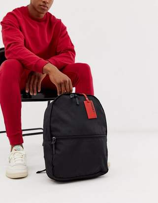 Asos Design DESIGN backpack in black with red luggage tag