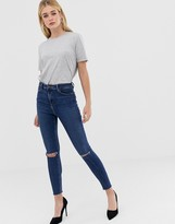 Asos DESIGN Ridley high waisted skinny jeans in dark wash blue with ripped knee detail