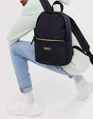 Asos Design DESIGN mini backpack in black with gold metal logo