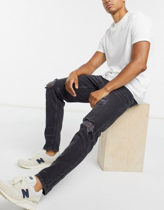 ASOS DESIGN rigid slim jeans in washed black with heavy rips