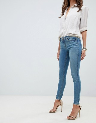 ASOS DESIGN whitby low rise 'skinny' jeans in mid stonewash blue
