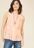 10174704 Throw your worries out the window and follow your bliss right into this loose and lovely tank top! This easy button-up boasts a delightfully ruffled hem and a bright peachy-pink color with white flowers strewn about, but its real statement is the lapels l