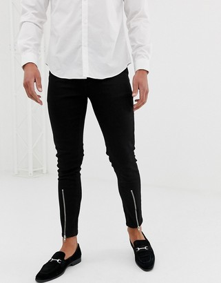ASOS DESIGN skinny jeans with zipped hem detail in black