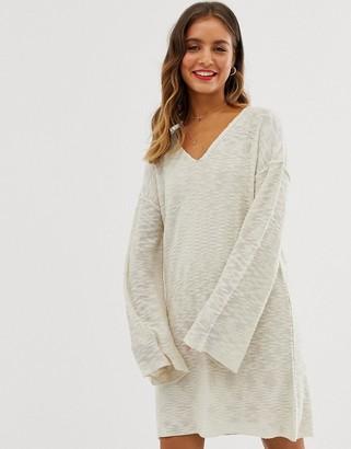Asos Design DESIGN v neck flare sleeve mini dress in natural look yarn-Stone